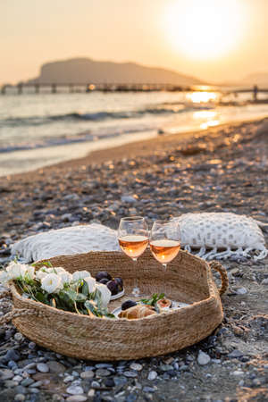 Vertical image of the beach picnic with wine, figs, croissants and camamber cheese in a woven basket.