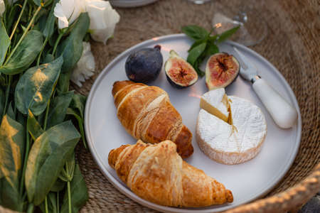 Horizontal image of croissants, figs and camamber cheese in a minimalistic white plate. 版權商用圖片