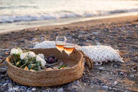 Horizontal image of the beach picnic with wine, figs, croissants and lisianthus flowers in a woven basket. Negative space. 版權商用圖片