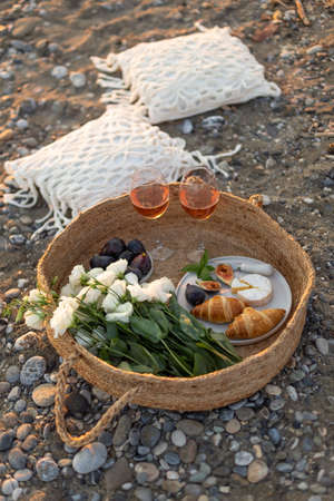 Vertical image of a beach picnic with croissants, figs, camamber cheese, rose wine and white lisianthus flowers in a woven basket.