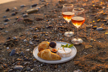 Horizontal image of a romantic beach picnic for two at sunset with two glasses of rose wine, croissants, camamber cheese and figs. Negative space. 版權商用圖片