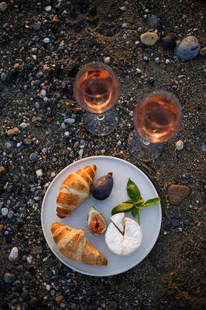 Upper view image of an outdoor picnic with wine, croissants, camamber cheese, and figs.