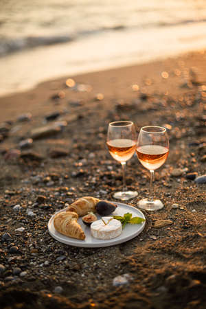 Beach picnic with rose wine, croissants, camamber cheese and figs. Negative space.