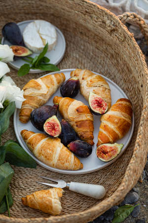 Upper view shot of a delicious breakfast with croissants and figs served with cheese in a woven basket.