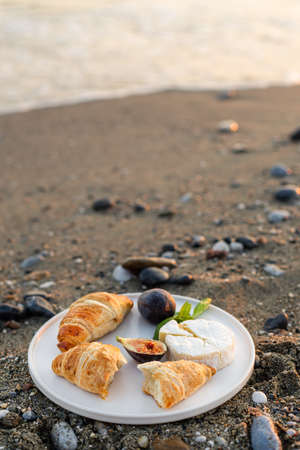 Vertical image of the beach picnic with figs, croissants and camamber cheese. Negative space.