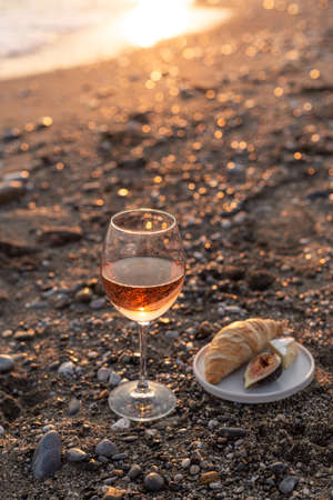 Vertical image of a glass of rose wine served with croissant and figs on the beach at sunset.