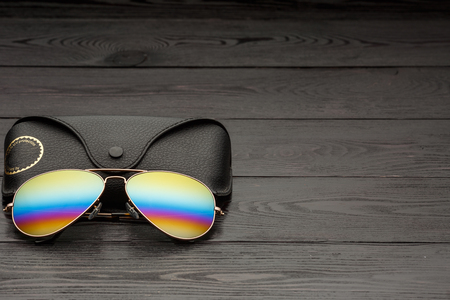 aviators sunglasses with mirrored color lenses made of glass in a gold metal frame covered with gold matte dusting on a black wooden background or table with a black leather case with a clip fastener with a gold circle and an inscription on a leather texture case