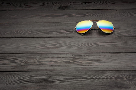 aviators sunglasses with mirrored color lenses made of glass in a gold metal frame and covered with a gold matte finish on a black wooden background or table