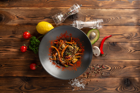wok vegetables in a black plate on a wooden background