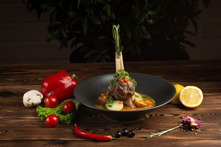 baked lamb shank with oriental herbs with vegetables on wooden background