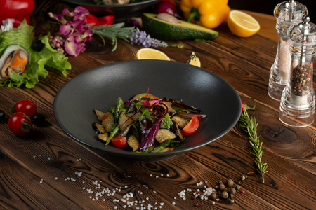 warm baked eggplant salad in a black plate on a wooden background