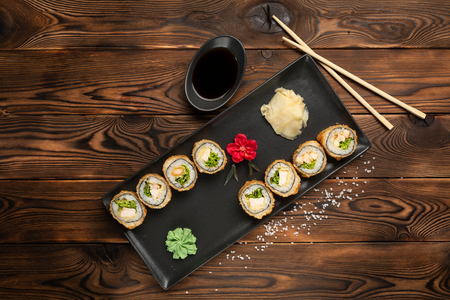 a set of rolls with cheese and herbs on a rectangular black plate on a black wooden background