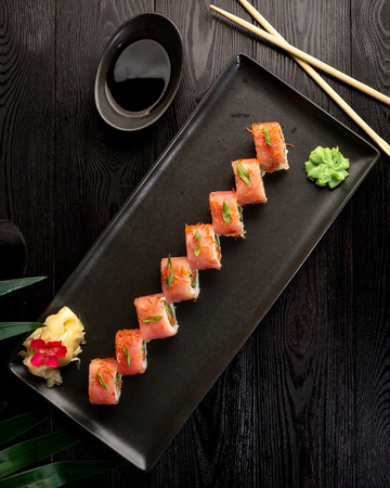 set of sushi rolls on a black rectangular plate on a black wooden background