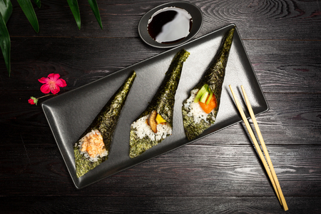 Temaki mix with salmon, eel and shrimp on a dark wooden background 스톡 콘텐츠