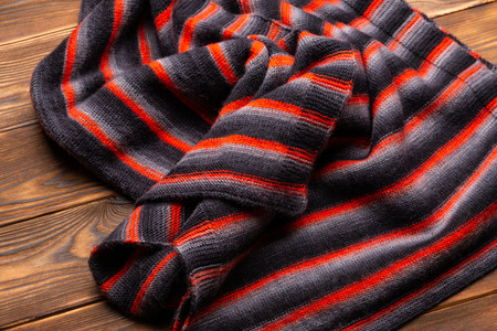 knitted scarf in black and red stripes on a wooden background Reklamní fotografie