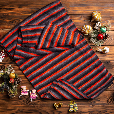knitted scarf in black and red stripes and christmas decorations on a wooden background Standard-Bild - 121001656
