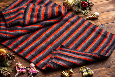 knitted scarf in black and red stripes and christmas decorations on a wooden background