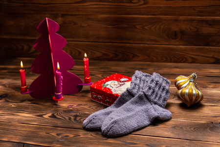 gray knitted socks, Christmas decorations and a metal box with the image of Santa on a wooden background