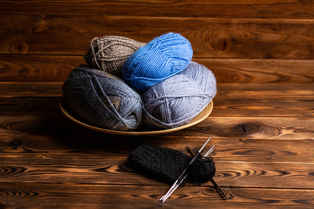 balls of gray and blue threads in a wooden plate and knitting needles with knitting on a wooden background