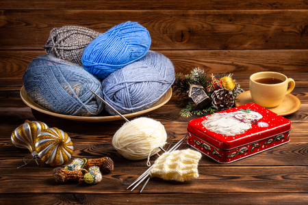 balls of gray and blue threads in a wooden plate, Christmas decorations, cup of tea and a metal box with a picture of Santa Claus knitting needles with a knitting on a wooden background