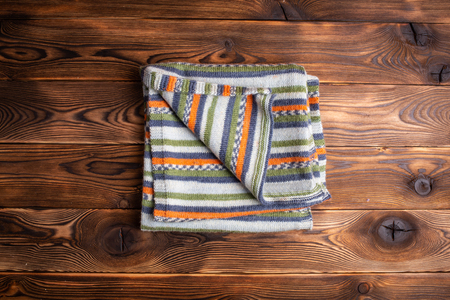 knitted scarf with colored stripes on a wooden background