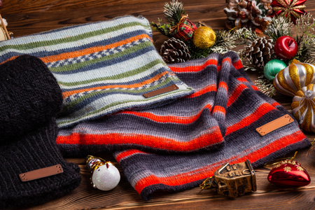 knitted striped striped scarves, black knitted sleeves and Christmas toys on wooden background