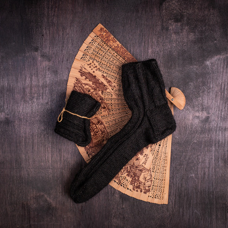 black knitted socks and a fan on a black and gray background