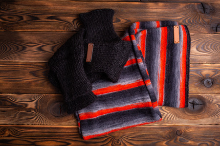 knitted scarf in black and red stripes and black knitted oversleeves on wooden background
