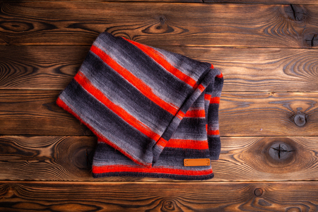 knitted scarf in black and red stripes on a wooden background Stockfoto