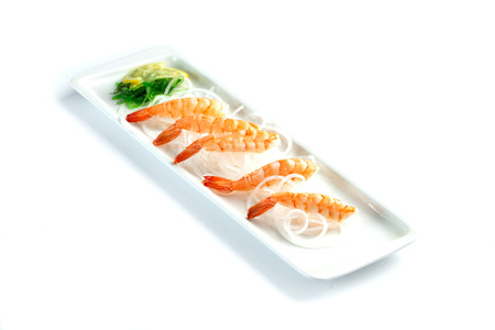 shrimps with lemon on a rectangular plate on an isolated white background