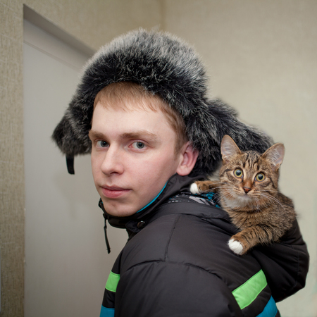young man with red hair wearing a hat with earflaps with fur with a tabby color kitten in the hood of his black jacket 免版税图像