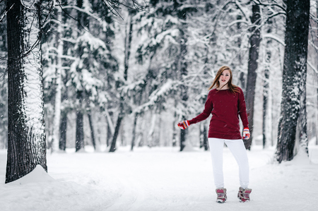 the beautiful girl dressed in a maroon sweater and white pants stands against the tree trunk against a backdrop of snow-covered winter forest