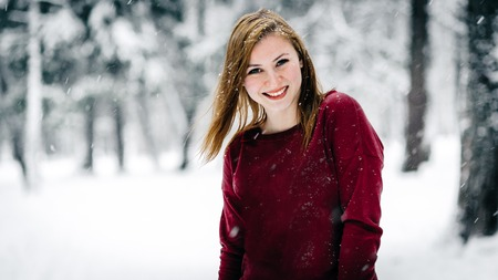 the beautiful girl dressed in a maroon sweater stands against the tree trunk against a backdrop of snow-covered winter forest