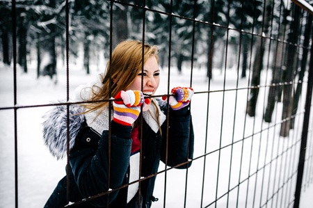 the beautiful girl keeps the hands behind the fence of metal bars on the background of the winter forest