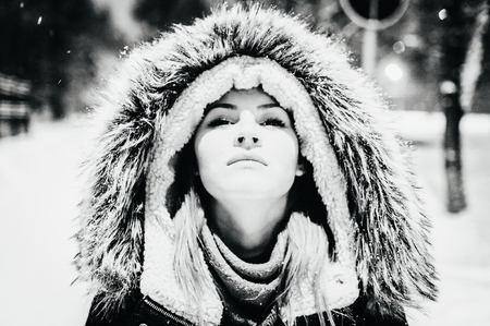 beautiful girl in fur hood. black and white portrait, close-up