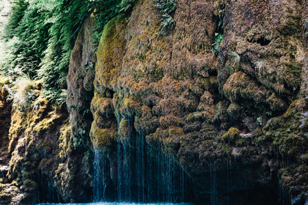 Waterfall flowing down a mountain covered with moss and vegetation. Sulak Canyon, Dagestan