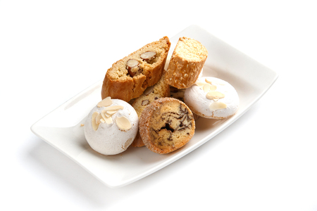 meringue and nut cookies in a white rectangular plate on an isolated white background