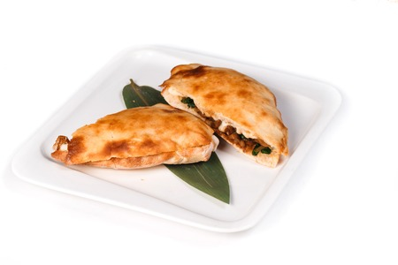 Calzone pizza halves on bamboo sheet in square plate on isolated white background