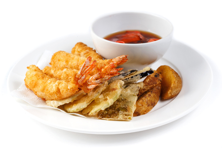 Camarones rebozados y una taza con salsa de soja y jengibre en un plato blanco sobre un fondo blanco aislado