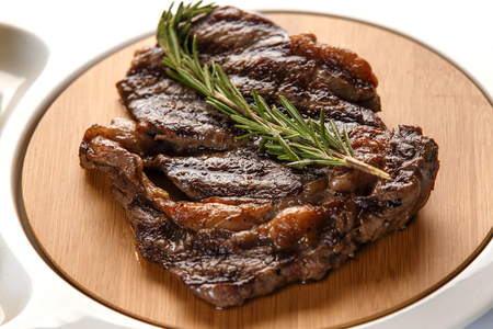 ribeye steak decorated with a sprig of rosemary on wooden background closeup