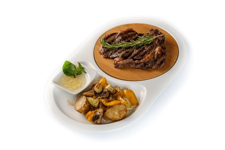 ribeye steak decorated with a sprig of rosemary with fried potatoes in a white oval plate on an isolated white background Stockfoto