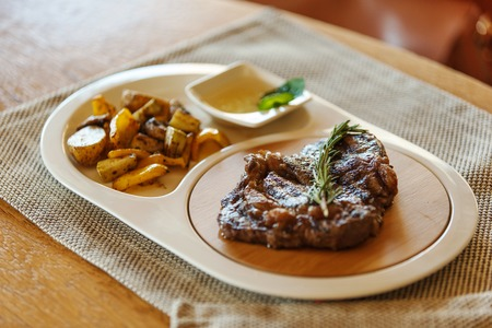 ribeye steak decorated with a sprig of rosemary with fried potatoes in a plate on a gray napkin on wooden background