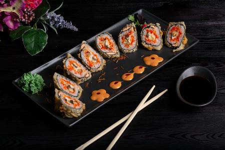 Placez des rouleaux de sushi sur une assiette rectangulaire noire, des baguettes et de la sauce soja sur un fond en bois foncé