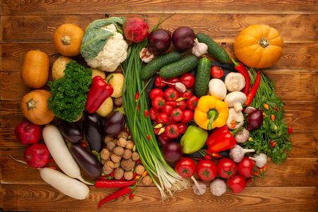 茶色の木の背景に新鮮な野菜やナッツ 写真素材