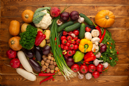 Fresh vegetables and nuts on a brown wooden background Stock Photo