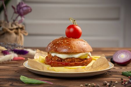 Cheeseburger from chopped beef cutlet with tomato. Light background. Close-up.