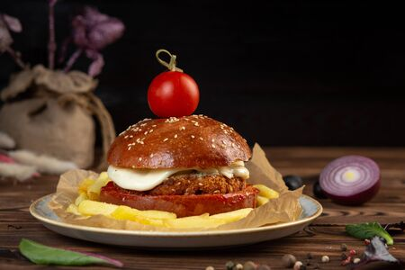 Cheeseburger from chopped beef cutlet with tomato. Dark background. Close-up.