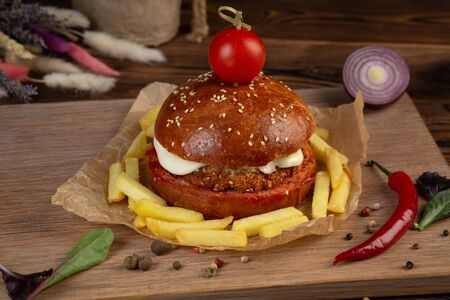 Cheeseburger from chopped beef cutlet with tomato. Wooden background. Close-up.
