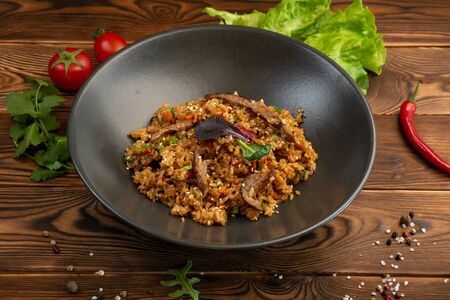 beef chahan fried Japanese rice with vegetables and slices of beef in a black plate on a wooden background