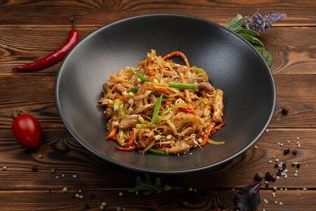 tori udon fried wheat noodles with chicken and vegetables and soy sauce in a black plate on a wooden background
